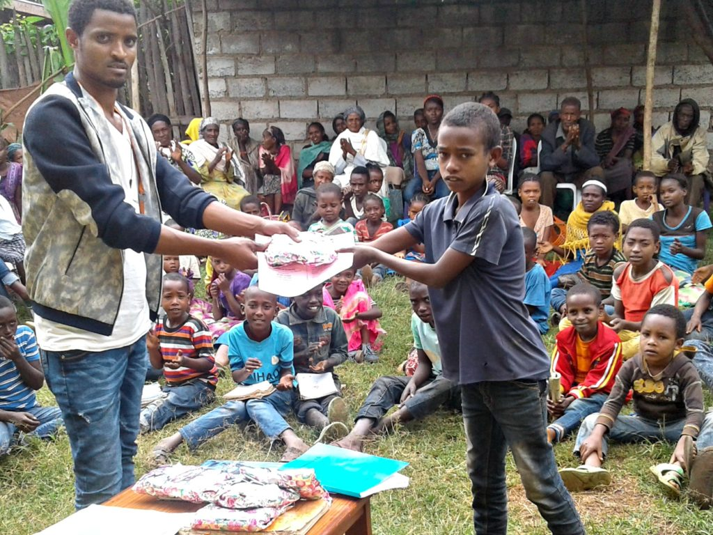 Girum receives his award from site coordinator Tesema Kuma